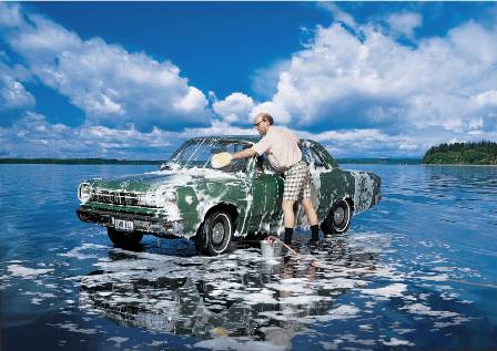 Man washing car on a body of water-symbolic