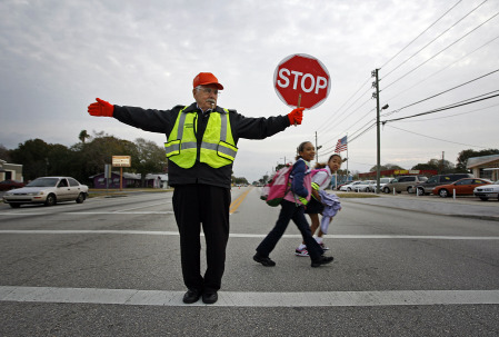 crossing guard assisting students across the street