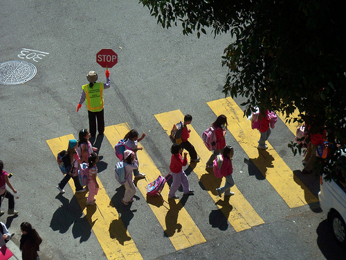students using a crosswalk with a crossing guard